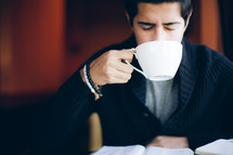 man holding a coffee mug to his mouth
