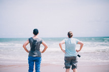 Women standing on the beach looking at the ocean.
