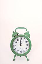green alarm clock at 12:00