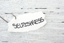 fish hook on paper with the word selfishness