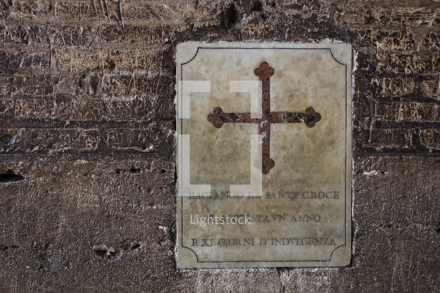 cross placard on a wall at the Coliseum in Rome
