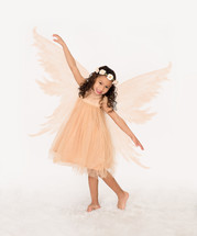 A little girl posing in a fairy costume.