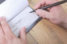 man writing a check to a church