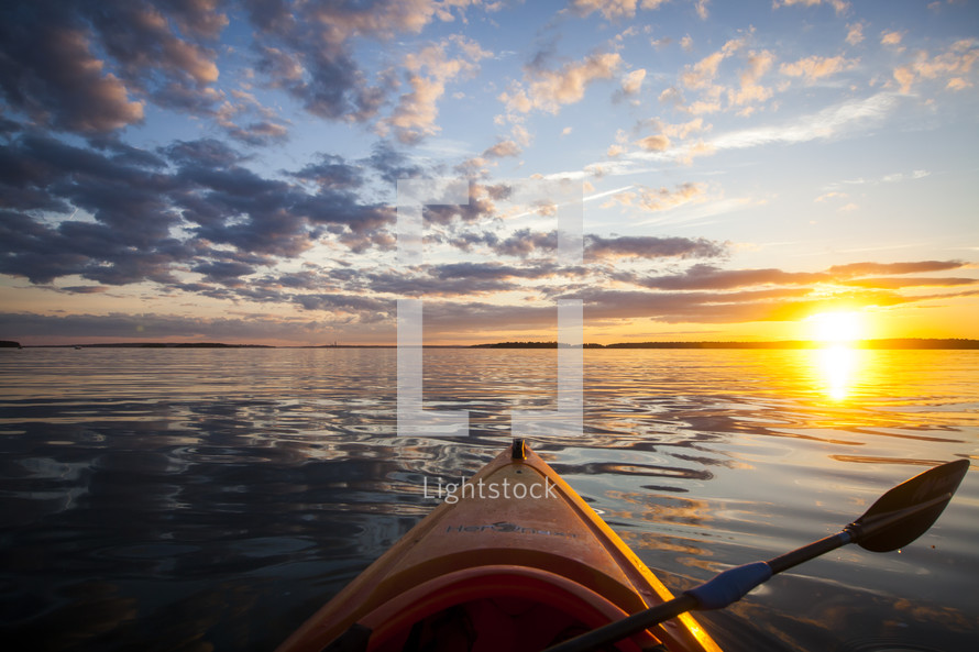 bow of a canoe on a lake at sunset