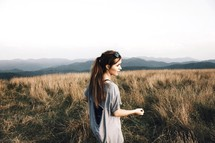 a woman walking through a field of tall grass on a mountain top