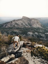 man climbing up a rock on the edge of a mountainside