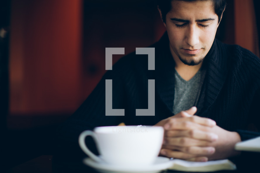 man with his hands held in prayer over a Bible and a coffee mug