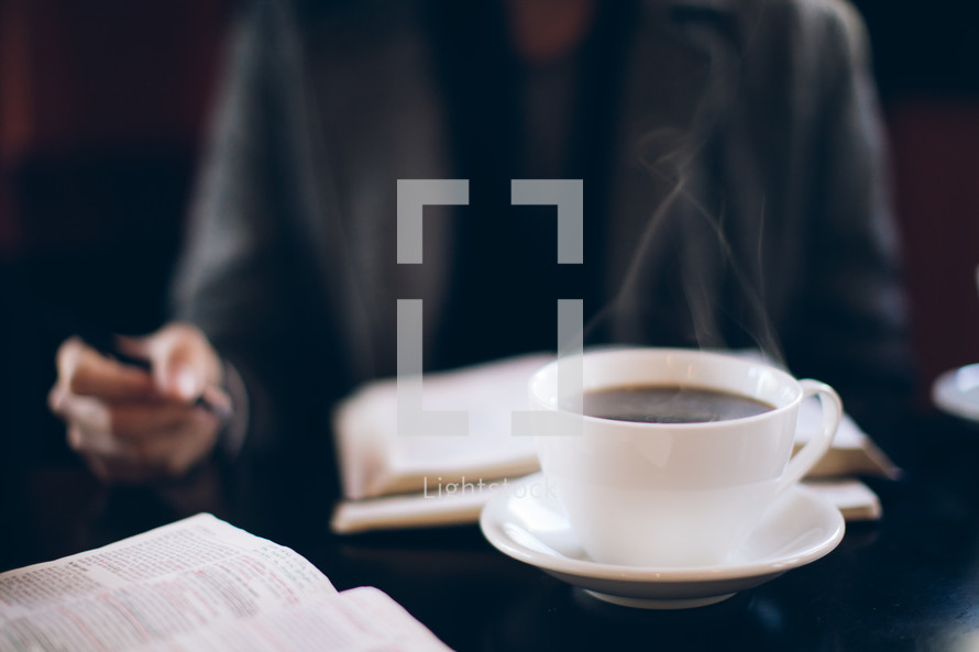 steam from a coffee mug and a man reading a Bible