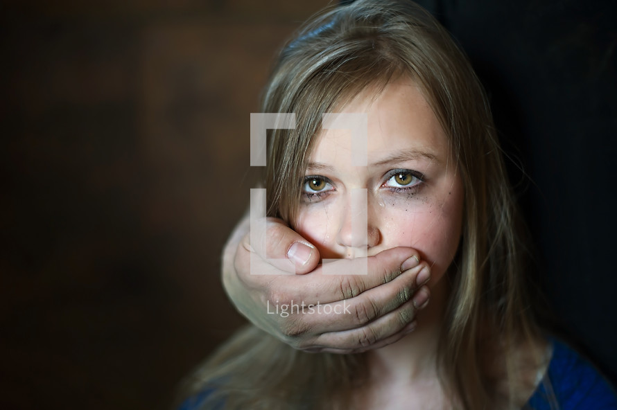 a hand over a teenage girls mouth