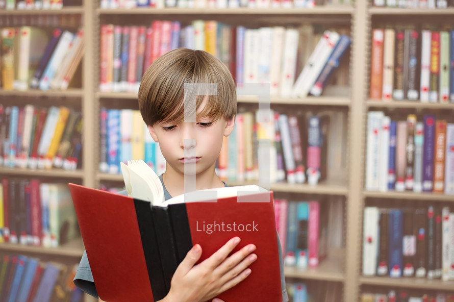 Boy reading a book in a library.