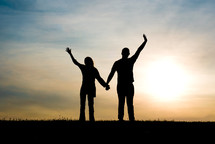 silhouette of a couple with raised hands