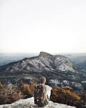 man sitting at the edge of a mountainside