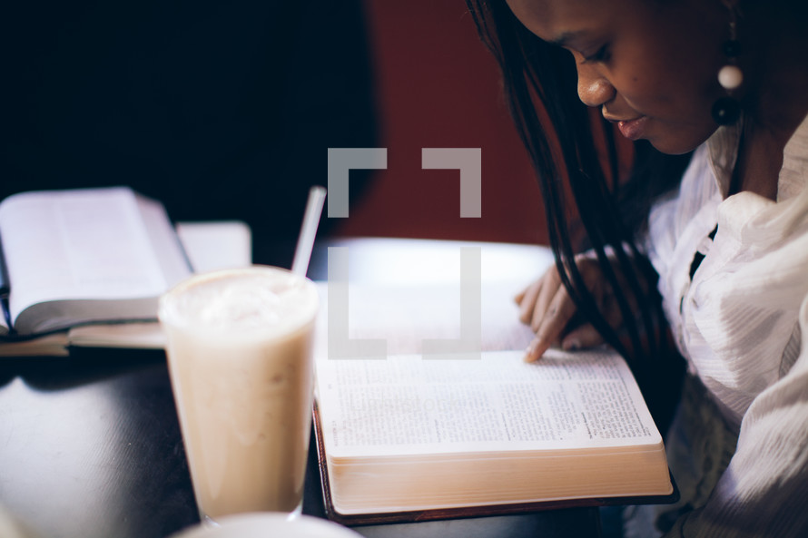 woman pointing to a Bible verse and reading a Bible