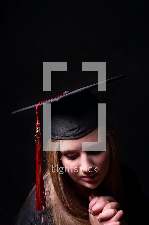 face of a female graduate in prayer