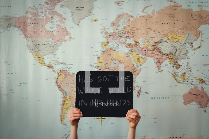 A girl in front of a world map holding a sign -... — Photo by Brown ...