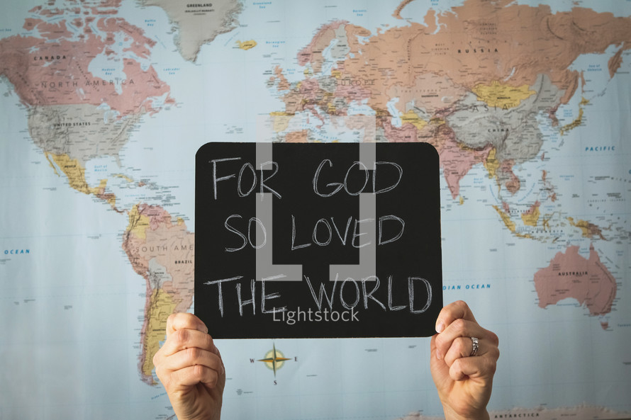 A woman in front of a world map holding a sign - For God so loved the world