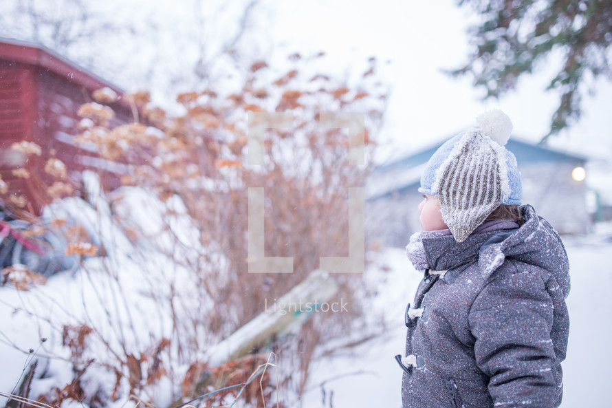 a boy child playing outdoors in snow