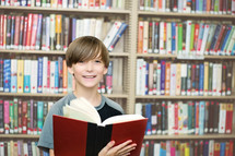 Smiling boy holding an open book in a library.