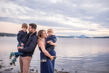 a young family standing by a lake shore