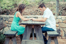 A young couple praying together at a picnic table.