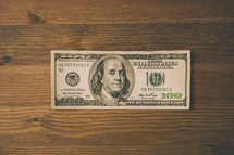 Hundred dollar bill on wood.