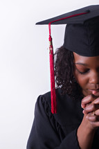 face of an African American graduate in prayer