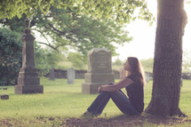 woman sitting in front of a tree in a cemetery