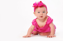 infant girl in fuchsia crawling