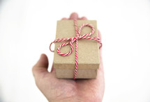 hand holding red and white string around a brown paper gift box