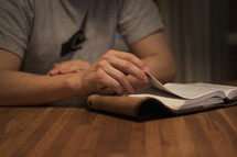 a man sitting at a table reading a Bible