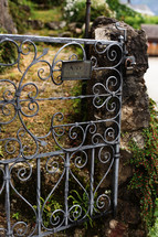 Wrought iron gate on a stone wall.