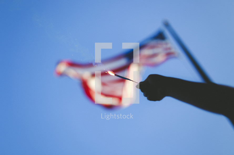 holding a sparkler in front of an American flag