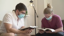 Men wearing face masks reading and discussing scripture