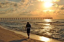 A beachcomber enjoys the solitude at daybreak near the fishing pier on Pensacola Beach, Florida.