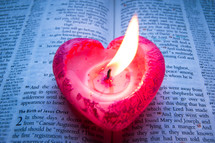 A pink heart-shaped candle burns on a bible opened at Luke chapter 2.