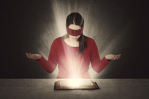 A woman reading a glowing Bible wearing a blindfold.