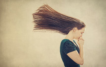 A woman in prayer as her hair is blown