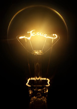 word Jesus in the filament of a glowing lightbulb