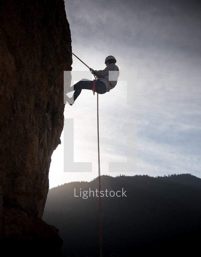 a woman scaling a steep cliff