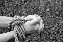 man with rope around his wrists praying