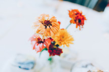 Flowers in a vase on a white tablecloth.