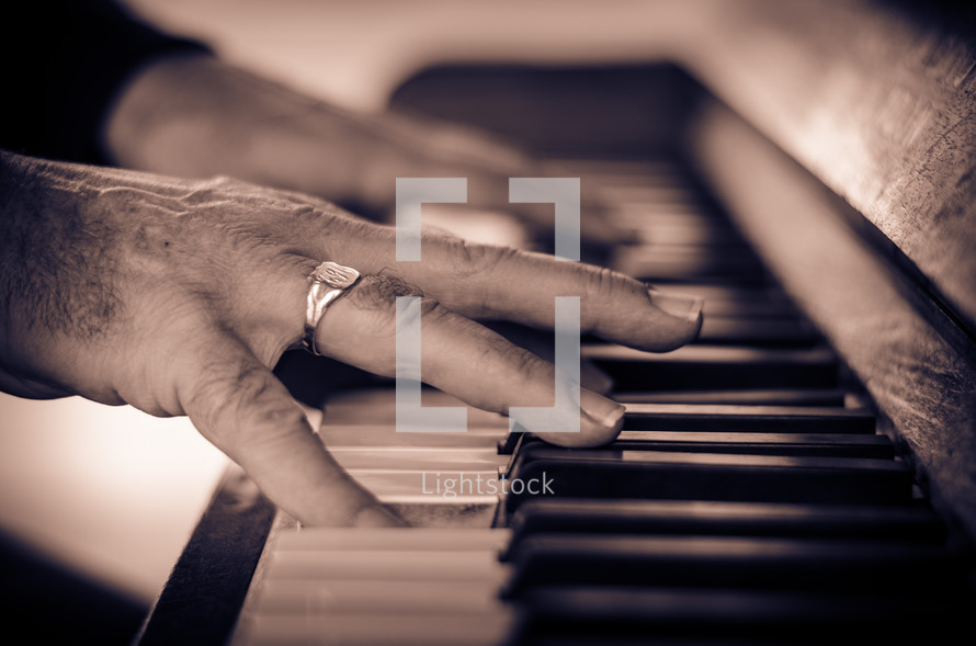 Man's hands playng the piano.