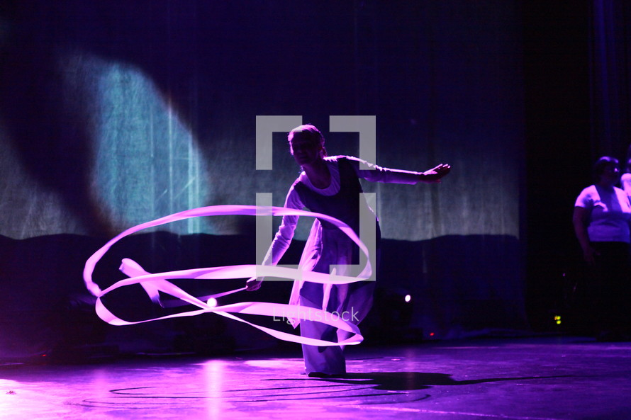 performer twirling a ribbon on stage