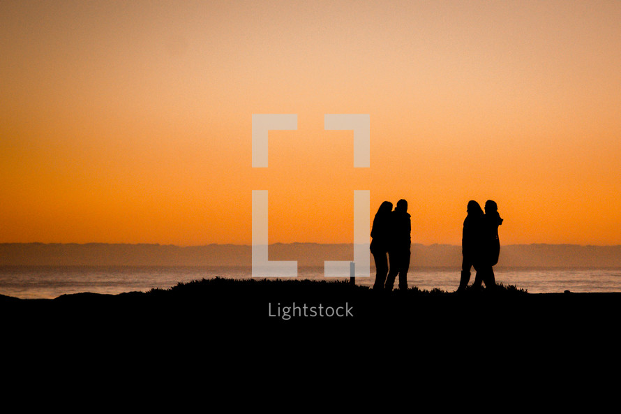silhouettes of people walking on a beach at sunset