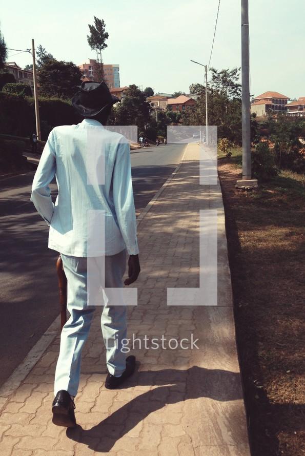 elderly man walking down a neighborhood sidewalk