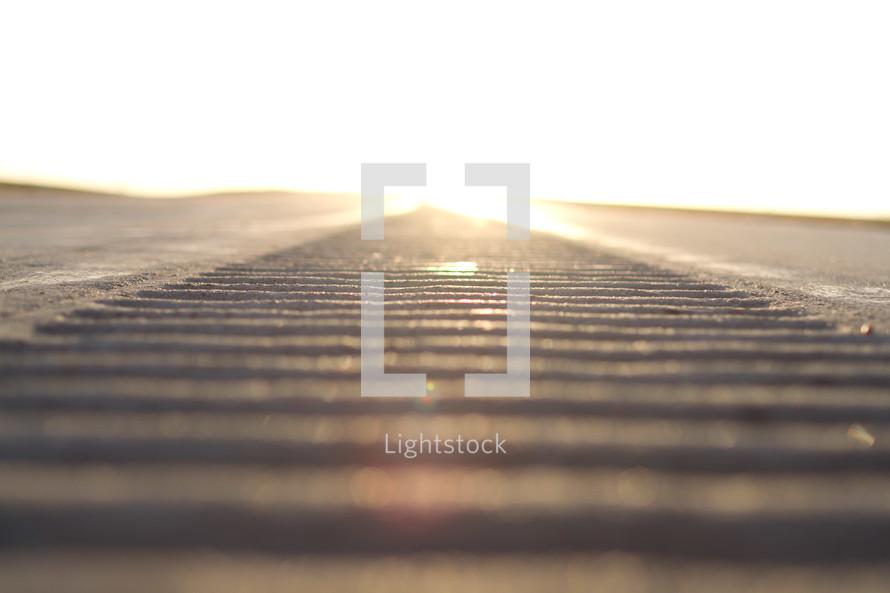 Rough concrete path looking into the sun