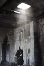 a man looking up at sunlight in an abandoned building