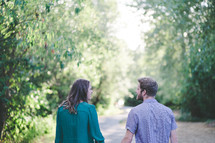 a couple walking hand in hand outdoors on a path