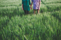 A man and woman holding hands in a field of green grass.