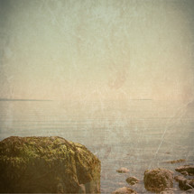 moss covered boulders on rocky ocean shore - vintage grunge for effect